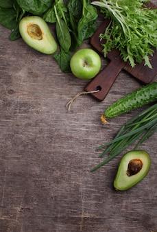 Verdura verde sana: espinaca, pepino, lechuga, manzana y aguacate en fondo oscuro. lay flat, copia espacio.