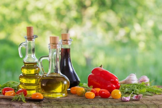 Verduras con aceite en la mesa de madera al aire libre
