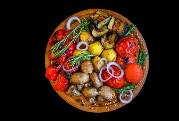Verduras al horno a la parrilla sobre una tabla de madera para el menú del restaurante