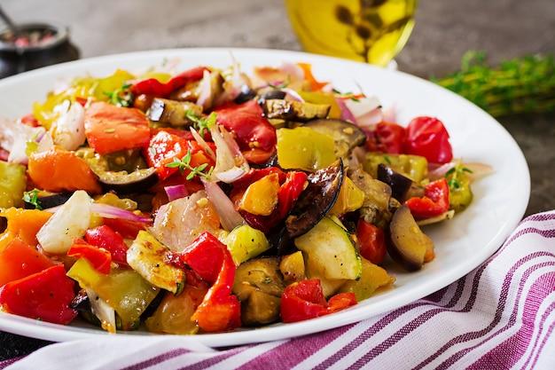 Verduras al horno en un plato blanco. berenjenas, calabacines, tomates, pimentón y cebolla.