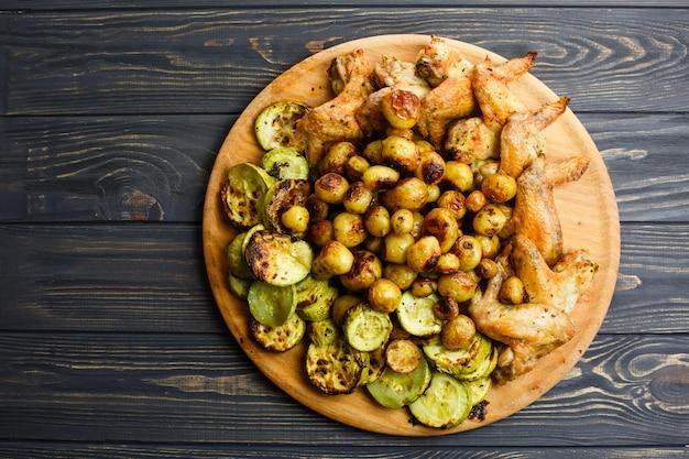 Verduras y alitas de pollo asadas a la parrilla en la placa de madera. espacio libre.