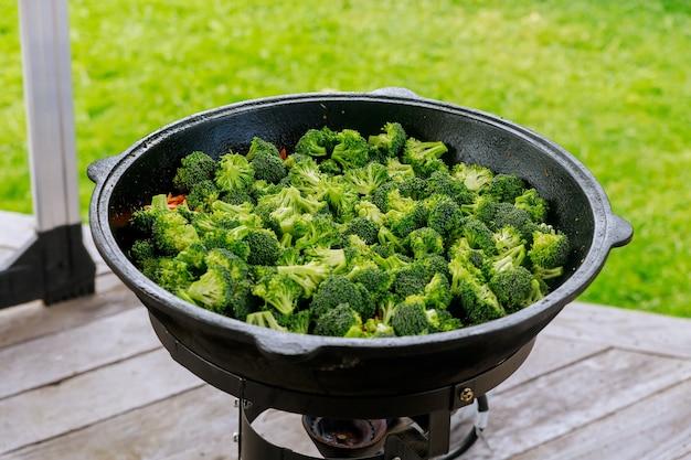 Verduras y brócoli cocinar en caldero en llamas al aire libre