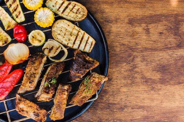 Verduras y carnes a la brasa en parrilla sobre mesa