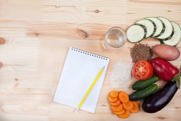 Verduras y cereales y cuaderno sobre una mesa de madera.