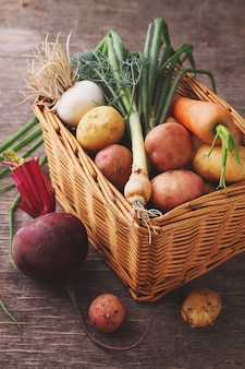 Verduras en una cesta: remolachas, cebollas, ajo, eneldo, papas, zanahorias en un fondo de madera vieja