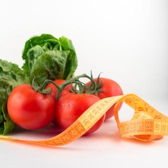 Verduras con cinta métrica en mesa de luz