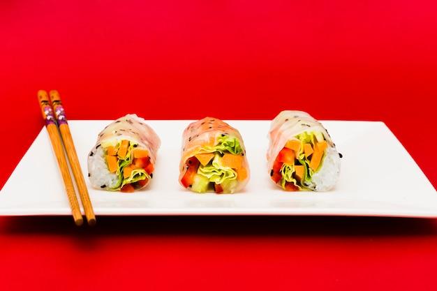Verduras coloridas rellenas en rollitos de primavera de arroz y palillos sobre plato blanco