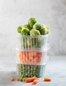 Verduras congeladas como guisantes verdes, coles de bruselas y zanahoria baby en las cajas de almacenamiento