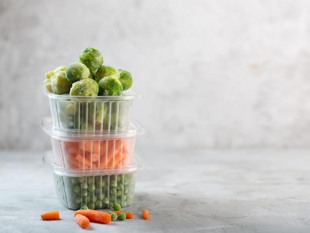 Verduras congeladas como guisantes verdes, coles de bruselas y zanahoria pequeña en las cajas de almacenamiento en el espacio gris concreto