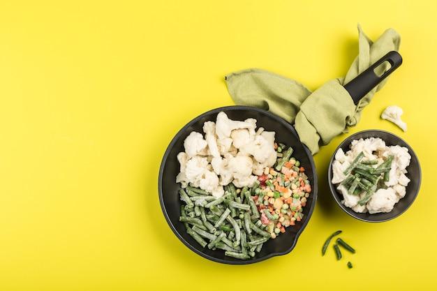 Verduras congeladas: judías verdes, coliflor y una mezcla de verduras en una sartén negra con una servilleta y en un plato sobre un fondo amarillo brillante.