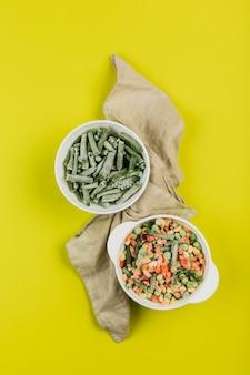 Verduras congeladas: judías verdes y una mezcla de verduras en platos blancos con una servilleta sobre un fondo amarillo brillante.