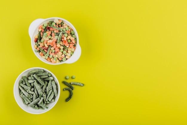 Verduras congeladas: judías verdes y una mezcla de verduras en tazones blancos sobre un fondo amarillo brillante.