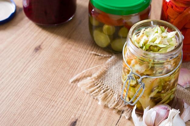 Verduras conservadas fermentadas en frasco en espacio de copia de mesa de madera
