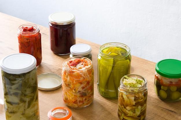 Verduras conservadas fermentadas en frasco sobre mesa de madera.