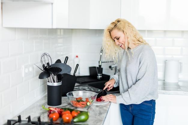 Verduras del corte de la mujer bastante rubia joven para la ensalada en casa en la cocina. concepto de comida sana.