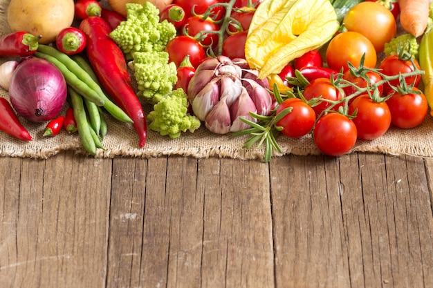 Verduras crudas en una mesa de madera de cerca con espacio de copia