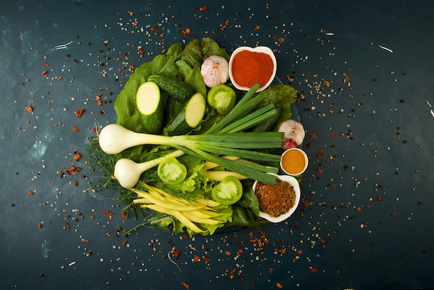 Verduras y especias frescas en una tabla de madera redonda en una piedra oscura. el concepto de vintage. especias el espárrago de maíz joven pepino de tomate verde en una superficie oscura.