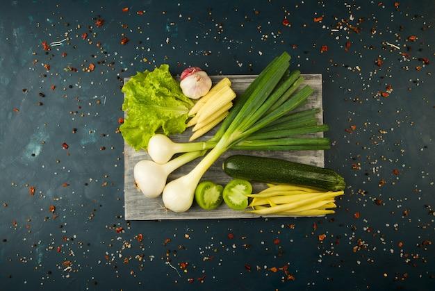 Verduras y especias frescas en un tablero de madera en una piedra oscura. el concepto de vintage. especias el espárrago de maíz joven pepino de tomate verde en una superficie oscura.