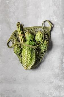 Verduras frescas en una bolsa de hilo verde. col de pekín, alcachofas y espárragos.