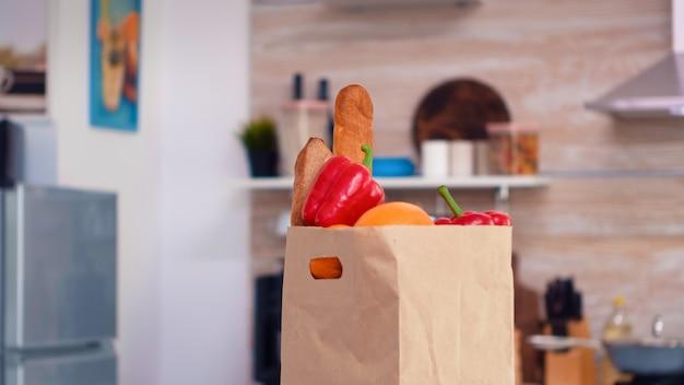 Verduras frescas en bolsa de papel en la mesa de la cocina. estilo de vida orgánico saludable compra joven de supermaket, bolsa de compras de comestibles de verduras frescas