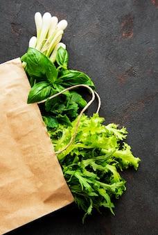 Verduras frescas en una bolsa de papel sobre una mesa negra
