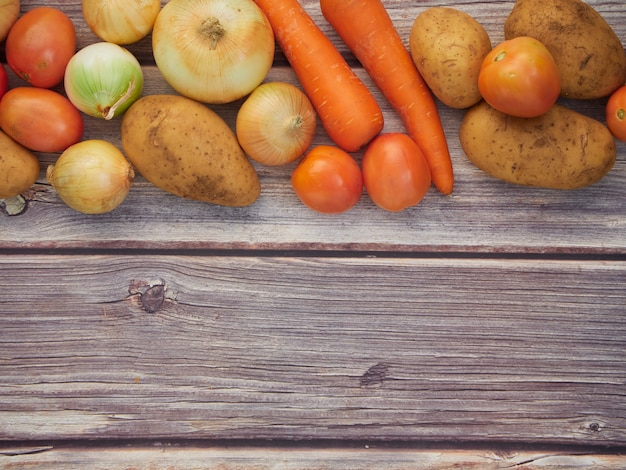 Verduras frescas, cebollas, tomates, zanahorias, papas, colocadas en una mesa de madera, vista superior