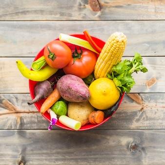 Verduras frescas de colores en un tazón sobre tablero de madera