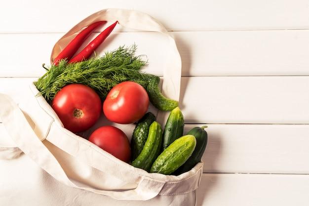 Verduras frescas en eco reutilizable cero residuos bolsa de compras textil sobre fondo blanco, orientación horizontal.