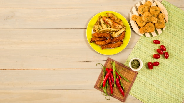 Verduras frescas y especias cerca de pollo asado y papas