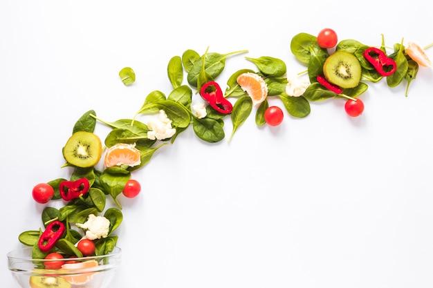 Verduras frescas y frutas dispuestas en forma curvada sobre fondo blanco