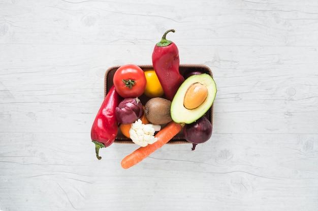 Verduras frescas y frutas en un recipiente sobre fondo blanco de madera
