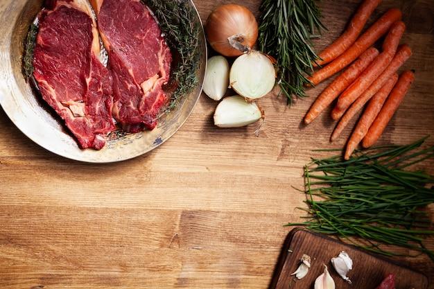 Verduras frescas junto a la carne cruda en placa de oro vintage. condimentado con sal y pimienta. cebolla blanca. tabla de madera.