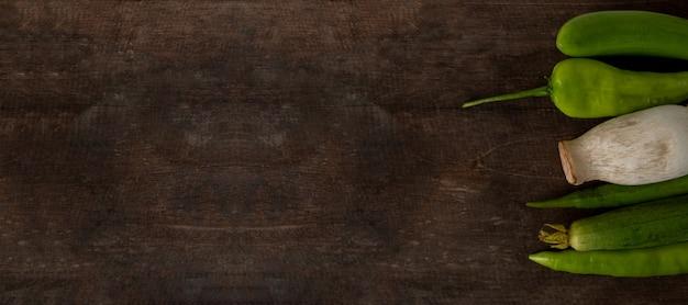 Verduras frescas listas para cocinar en el fondo de la mesa de madera rústica