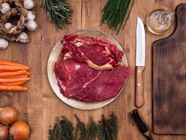 Verduras frescas en la mesa de madera con dos trozos de carne roja en el centro del marco. romero verde. proteína natural.