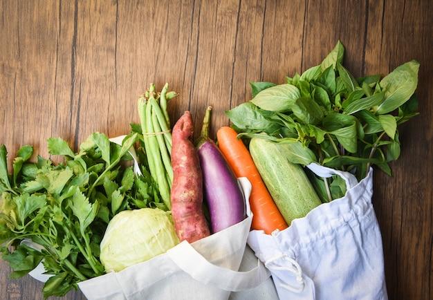 Verduras frescas orgánicas en bolsas de tela de algodón ecológico en mesa de madera