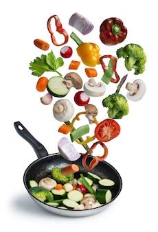 Verduras frescas a la parrilla volando aislado sobre fondo blanco.