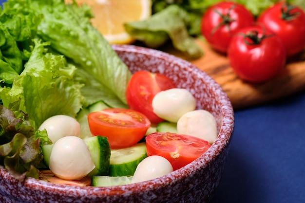 Verduras frescas y un plato de ensalada con mozzarella sobre un fondo azul. ensalada caprese . lechuga, tomates cherry, mozzarella,