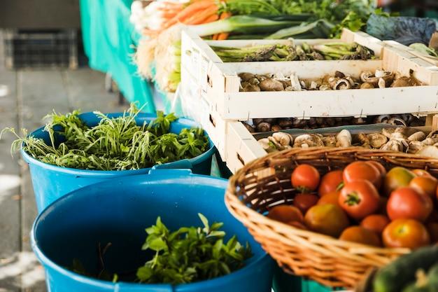 Verduras frescas con setas en cajón de madera en puesto de mercado
