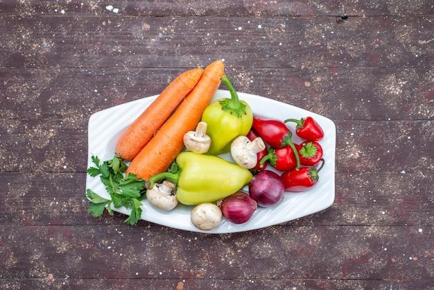 Verduras frescas con setas dentro de la placa en el escritorio marrón, comida vegetal seta