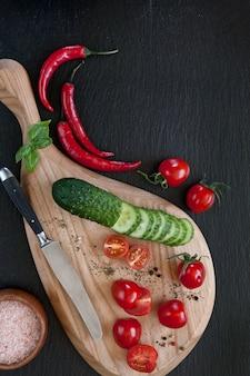 Verduras frescas en la tabla de cortar de madera con un cuchillo en el fondo concreto