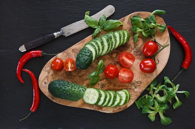 Verduras frescas en la tabla de cortar de madera con un cuchillo sobre fondo de hormigón negro
