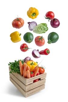 Verduras frescas volando en una caja de madera aislada