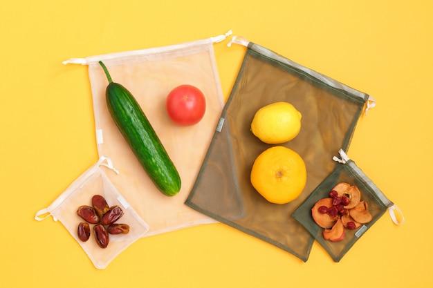 Verduras y frutas en bolsas de malla reutilizables ecológicas en la pared amarilla