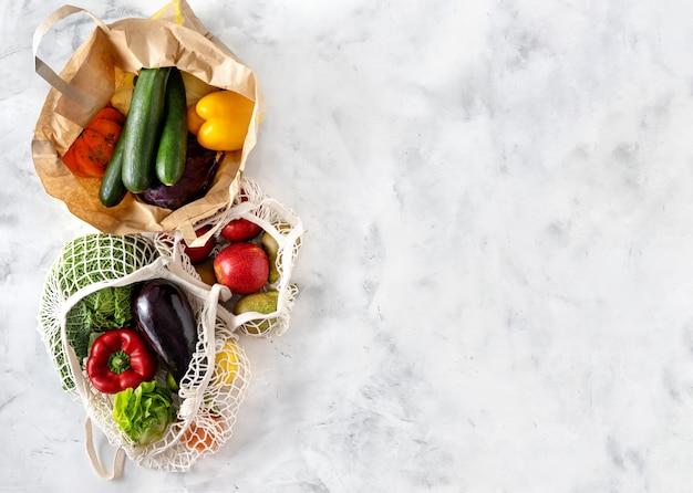 Verduras y frutas en bolsas de papel y red sobre fondo blanco.