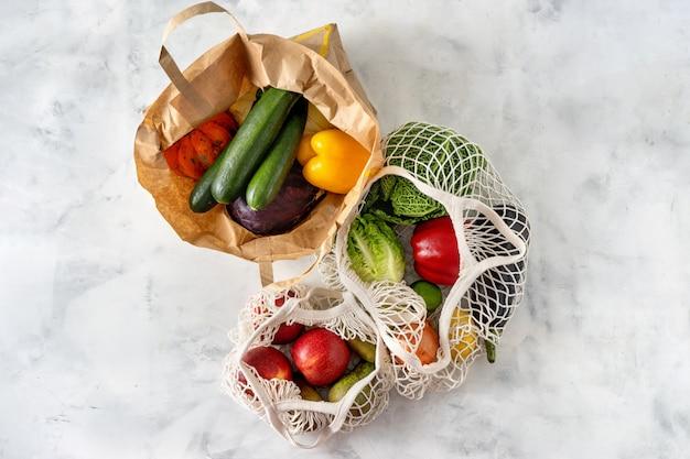 Verduras y frutas en bolsas de papel y red.