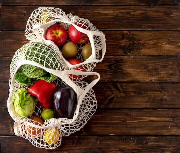 Verduras y frutas en bolsas de red sobre fondo rústico oscuro