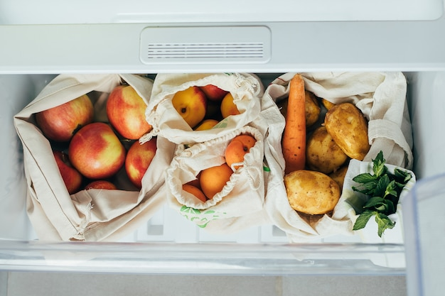 Verduras y frutas frescas en bolsas de algodón ecológico en un refrigerador
