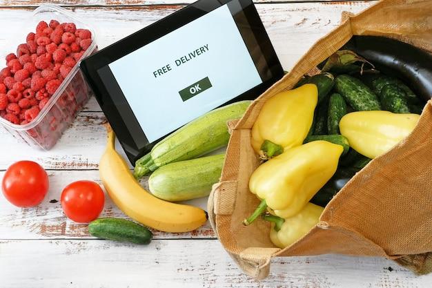Verduras y frutas orgánicas en bolsa de algodón y tablet pc, mercado en línea, entrega de comestibles verde en el concepto de hogar, primer plano