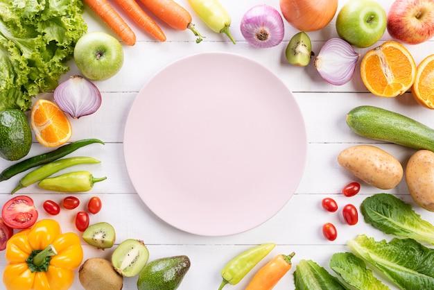 Verduras y frutas sobre madera blanca.
