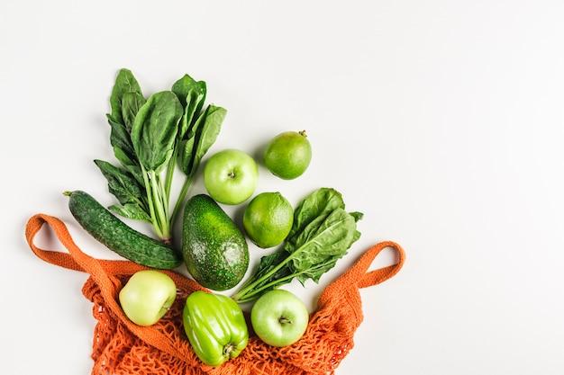 Verduras y frutas verdes en bolsa de hilo naranja
